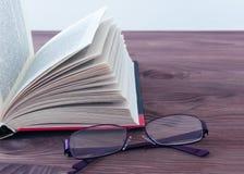 Geopend boek, die op een houten achtergrond liggen Stock Foto