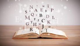 Geopend boek met vliegende brieven stock foto