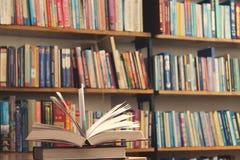 Geopend boek op de boekenrekachtergrond royalty-vrije stock afbeeldingen