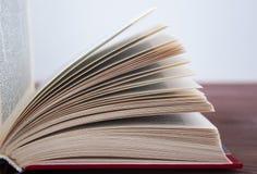 Geopend boek, op een houten achtergrond met het stemmen Stock Afbeelding