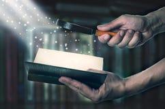 Geopend magisch boek met loupe magisch licht royalty-vrije stock fotografie