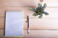 Geopend notitieboekje met een uiterst kleine bloem op houten lijst Hoogste mening Wr Royalty-vrije Stock Foto's