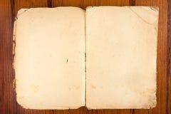 Geopend oud softcoverboek op een houten achtergrond Stock Foto's