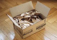 Geopend pakket van Amazonië op de vloer van het huisparket Stock Afbeeldingen