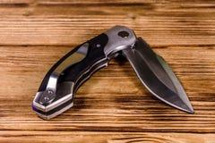 Geopend vouwend mes op een houten lijst stock foto