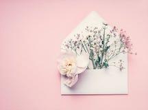 Geopend wikkel met bloemen regeling op pastelkleur roze achtergrond, hoogste mening, exemplaarruimte Creatieve groet, Uitnodiging Royalty-vrije Stock Fotografie