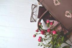 Geopende dame` s zak en bloemen op de witte houten achtergrond stock foto's