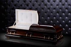 Geopende houten bruine sarcofaag die op grijze luxeachtergrond wordt geïsoleerd kist, doodskist op koninklijke achtergrond Stock Foto's