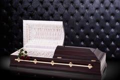 Geopende houten bruine sarcofaag met rode die rozen op grijze luxeachtergrond worden geïsoleerd kist, doodskist op koninklijke ac Stock Foto