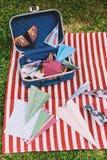 Geopende Koffer met Kleurendocument Vliegtuigen op de Witte en Rode Strepenmat Royalty-vrije Stock Fotografie