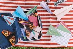 Geopende Koffer met Kleurendocument Vliegtuigen op de Witte en Rode Strepenmat Stock Foto