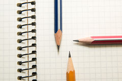 Geopende notitieboekje en potloden op over wit Royalty-vrije Stock Foto's