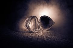 Geopende oude uitstekende zilveren hart-vormige kist voor trouwringen op donkere gestemde rokerige lichte achtergrond het concept Stock Afbeeldingen
