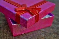 Geopende roze giftdoos met rood lint en het gouden stikken op de houten achtergrond als symbool van het geven en het krijgen van  Stock Foto