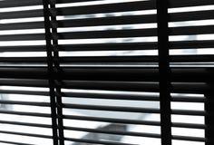 Geopende Venetiaanse plastic zonneblinden in zwart-wit Plastic venster met zonneblinden Binnenlands ontwerp van woonkamer met ven stock afbeelding