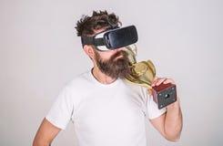 Geopende voltooiing Hoofdtelefoon van mensen houdt de gebaarde hipster vr gouden drinkbeker De virtuele concurrentie van de mense stock foto's