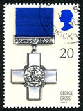 George Cross UK Postage Stamp. GREAT BRITAIN - CIRCA 1990: A used postage stamp from the UK, depicting an illustration of the George Cross medal awarded for Stock Images