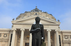 George Enescu statue during winter. Image of the George Enescu's statue during the winter season in front of the Romanian Atheneum building in Bucharest,Romania Stock Photo
