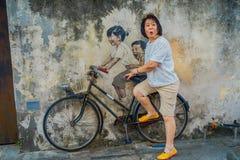 George Town, Malaysia - 10. März 2017: Kleine Kinder auf einem Fahrrad, populäre Wandstraßenkunst die unbekannte Touristen Stockfoto