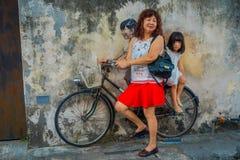 George Town, Malaysia - 10. März 2017: Kleine Kinder auf einem Fahrrad, populäre Wandstraßenkunst die unbekannte Touristen Stockbilder