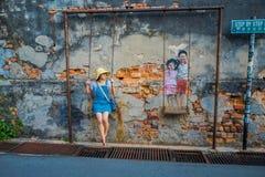 George Town, Malaysia - 10. März 2017: Unbekannte Frau touristisch und die Kinder auf der Schwingenwandstraßenkunst stockbild