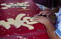 Craftsman carving wood at factory stock photos