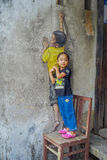 George Town, Malaysia - March 10, 2017: Unknown girl posing with street art graffiti of boy on a chair in George Town Royalty Free Stock Image