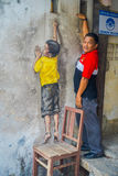 George Town, Malaysia - March 10, 2017: Unknown man posing with street art graffiti of boy on a chair in George Town Royalty Free Stock Photo