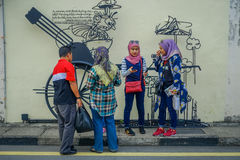 George Town, Malaysia - March 10, 2017: Unknown muslim tourists standing by Cannon graffiti, street art and iron. Sculpture in Cannon street Stock Photo