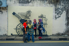 George Town, Malaysia - March 10, 2017: Unknown muslim tourists standing by Cannon graffiti, street art and iron. Sculpture in Cannon street Royalty Free Stock Image