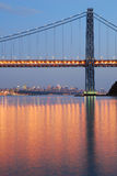 George Washington Bridge with NYC skyline at dusk. With evening light reflecting in Hudson river stock photography