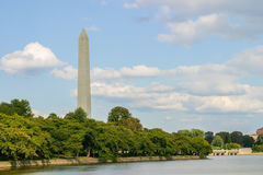 George Washington Monument. The George Washington Monument in Washington DC summertime green trees and replace green shrubbery Bluewater in the foreground blue Royalty Free Stock Image