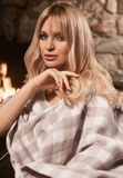 Georgeous elegant blonde under bright plaid near fireplace Stock Photography
