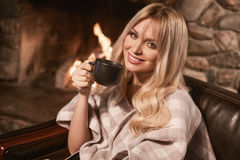 Georgeous elegant blonde under bright plaid near fireplace. Portrait of georgeous elegant blonde under bright plaid with cup of tea near the cozy fireplace Royalty Free Stock Photography