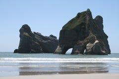 Georgeous plaża z rockową wyspy whith trawą i dziurami zdjęcia royalty free