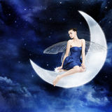 Georgeouse young woman as fairy on the moon. Georgeouse young woman as fairy sitting on the moon, night sky royalty free stock images