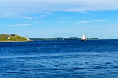 Georges Island lighthouse, and a sailboat, in Halifax. View of Georges Island lighthouse, and a sailboat, in Halifax, Nova Scotia, Canada royalty free stock photos