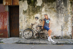 Georgetown, Malaysia - 07 September 2016: Tourist with street art. Georgetown, Penang, Malaysia - 07 September 2016: Female tourist pose with street art royalty free stock photo