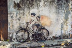 Georgetown, Penang, Malaysia - April 20, 2018: Public street art Name Children on a bicycle painted 3D on the wall that`s two lit. Tle Chinese girls riding stock image