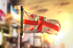 Georgia Flag Against City Blurred Background At Sunrise Backligh. T Sky Royalty Free Stock Photo