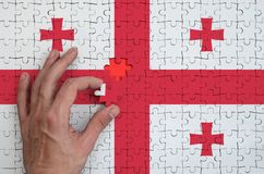 Georgia flag is depicted on a puzzle, which the man`s hand completes to fold.  vector illustration