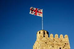 The Georgia flag on the roof of an ancient tower against the clear blue sky. Stock Images