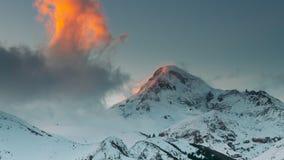 georgia Pico del soporte Kazbek durante puesta del sol por la tarde del invierno Paisaje georgiano hermoso almacen de video