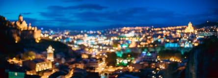 Georgia tbilisi Абстрактный фон Bokeh панорамы крепости Narikala, собора святой троицы Sameba в вечере стоковые изображения