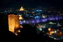 Georgia, Tbilisi - 05.02.2019. - Night view from Narikala fortress. Abanotubani, sulfur baths and holy trinity Sameba church in stock photography