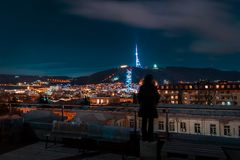 Georgia, Tbilisi - 05 02 2019 - Opinión del paisaje urbano de la noche con la situación humana de la silueta en el tejado Las señ imagenes de archivo