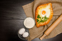 Georgian cuisine. Top view of khachapuri on sackcloth, flour, eggs and rolling pin. Black table, space for text.  royalty free stock images