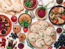 Georgian cuisine on white table top view. View from above of georgian cuisine on white wooden table. Traditional georgian cuisine and food - khinkali, kharcho stock photography