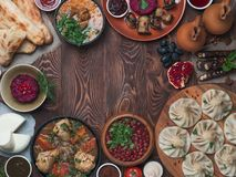 Georgian cuisine on wood table,top view,copy space. View from above of georgian cuisine on brown wooden table.Traditional georgian food-khinkali,kharcho Stock Images