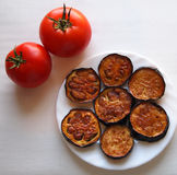 Georgian dish, fried eggplant with tomatoes. Georgian dish, fried eggplant in olive oil with tomato on a white plate, fresh tomatoes, light meal, snacks Royalty Free Stock Photos